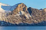 Fishing boat sails in Mefjorden with imposing rock walls behind it. Mefjordvaer, Mefjorden, Senja, Norway, Europe.