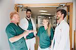 Cheerful medical colleagues talking in hospital corridor