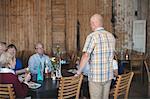 Senior man giving speech to friends while having lunch in restaurant
