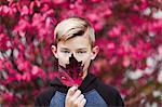 Portrait of boy holding leaf over mouth