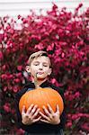 Portrait of boy holding pumpkin