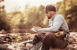 Fisherman sitting on river rocks looking at smartphone, Mozirje, Brezovica, Slovenia