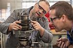 Male car mechanics pointing at car part in repair garage