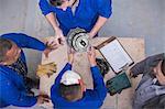 Overhead view of car mechanic team inspecting car part in repair garage