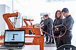 Robotics apprentices using test industrial robots in robotics facility
