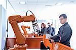 Robotics apprentice with robot in robotics facility