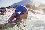 Determined female open water swimmer swimming in sunny ocean
