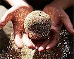 Hands cupping golden glitter apple