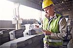 Steelworker writing on clipboard in steel mill