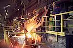 Steelworker on platform above molten furnace in steel mill