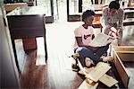 Women reading instructions, assembling furniture