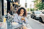 Woman at pavement cafe, Milan, Italy