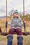 Girl sitting on swing in rural setting