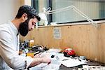 Man at workbench assembling object