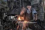 Blacksmith hammering hot iron bar on anvil at workshop