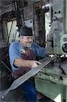 Blacksmith hammering red hot iron bar in hammer machine at workshop
