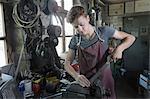 Blacksmith apprentice rasping iron fixed in plain vise