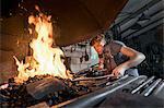 Blacksmith apprentice lightning fire in furnace at workshop