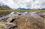 Clouds on rocky peaks reflected in the alpine Lake Schottensee, Fluela Pass, canton of Graubunden, Engadine, Switzerland, Europe