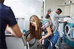 University friends doing laundry at laundromat