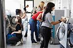 Multi-ethnic university students doing laundry at laundromat