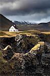 Lone house and sea stacks in stormy weather, Arnastapi, Snaefellsnes Peninsula, Iceland, Polar Regions