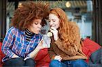 Friends sharing drink through drinking straws
