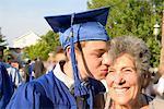 Teenage boy kissing grandmother at graduation ceremony