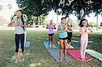 Girls and teenage schoolgirls practicing yoga mountain pose on school playing field
