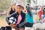 Portrait of schoolgirl amongst group holding soccer ball on school sports field