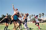 Schoolgirl soccer team celebrating on school sports field