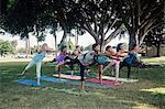 Schoolgirls practicing yoga warrior three pose on school sports field
