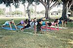 Schoolgirls practicing yoga plank pose on school sports field