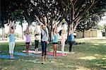 Schoolgirls practicing yoga pose on school sports field