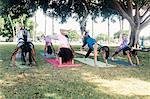 Schoolgirls practicing yoga downward facing dog on school sports field