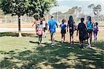 Rear view of teacher and schoolgirls walking to soccer practice on school sports field