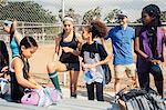 Teacher and schoolgirls soccer players preparing for practice on school sports field