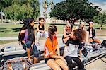 Schoolgirl soccer players chatting on school sports field bench