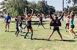 Schoolgirl soccer players warming up on school sports field