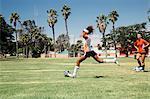 Teenage schoolgirl kicking soccer ball on school sports field