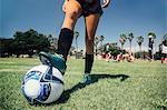 Waist down of teenage schoolgirl soccer player with foot on ball on school sports field