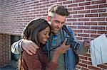 Man and woman outdoors, looking at back of digital camera, smiling