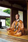 Buddhist monk with shaved head wearing golden robe sitting cross legged on the floor, meditating, Buddhist hand gesture.