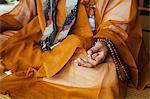 Close up of Buddhist monk wearing golden robe sitting cross legged on the floor, meditating, Buddhist hand gesture.