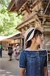 Young woman wearing blue dress and hat at Shinto Sakurai Shrine, Fukuoka, Japan.