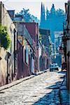 Car on traditional cobblestone street in San Miguel de Allende, Mexico