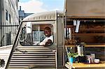 Portrait of smiling salesman sitting in food truck