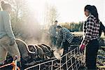 Multi-ethnic male and female farmers feeding pigs at organic farm