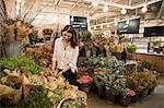 Woman choosing flowers in shop