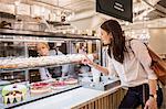 Woman choosing cake in bakery